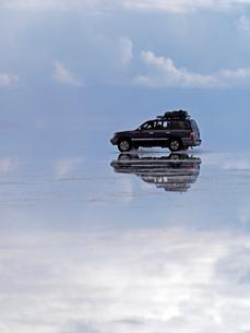 南米ウユニ塩湖の鏡張りの湖面を走る四輪駆動車の写真素材 [FYI03131281]
