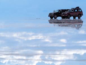 塩湖の鏡張りに写る青空と雲に浮かぶように見える四輪駆動車の写真素材 [FYI03131286]