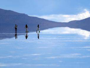 南米ウユニ塩湖の鏡張りの上に見える観光客の写真素材 [FYI03131289]