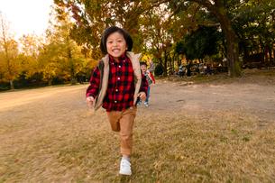 秋の公園をかけっこする子供の写真素材 [FYI03131357]