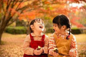 秋の公園で焼き芋を持つ子供の写真素材 [FYI03131383]