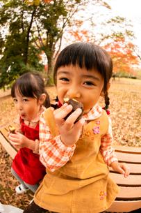 秋の公園で焼き芋を食べる子供の写真素材 [FYI03131387]