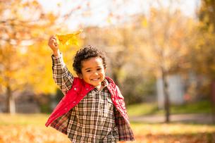 落ち葉の公園を走る子供の写真素材 [FYI03131445]