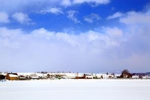 富良野国道より望む青空と雪の住宅街遠望の写真素材 [FYI03131813]