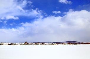 富良野国道より望む青空と雪の住宅街遠望の写真素材 [FYI03131815]