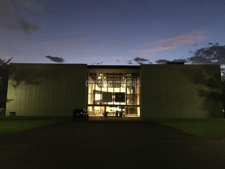 夕暮れに染まる空、佇む建築から漏れるあたたかい光の写真素材 [FYI03132312]