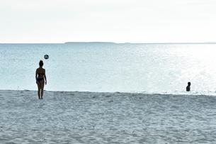 透明感のあるウヴェア島のビーチでボール遊びをするビキニの女性と遠くに見える島影の写真素材 [FYI03132592]
