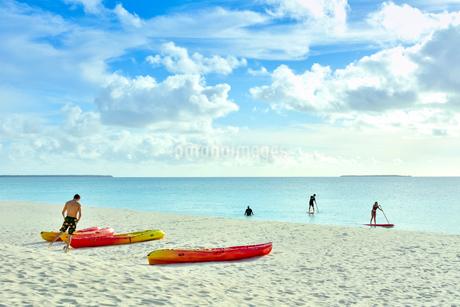 ウヴェア島の透き通った青い海でカヌーで遊ぶ若者たちと青い空とたなびく雲の写真素材 [FYI03132599]