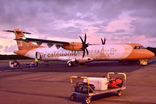 赤く染まった空港で出発の準備のため荷物の積み込みがされる飛行機の写真素材 [FYI03132607]