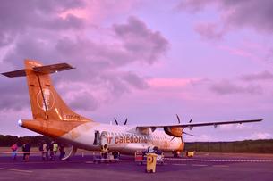 赤く染まった空港で出発の準備のため荷物の積み込みがされる飛行機と乗り込む乗客達の写真素材 [FYI03132610]