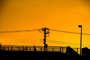 夕焼けと電線と建物のシルエットの写真素材 [FYI03132668]