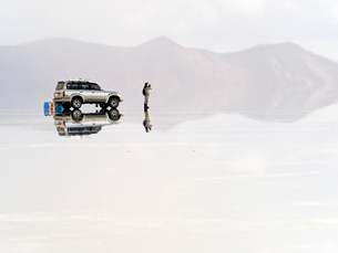 絶景南米ボリビアウユニ塩湖の鏡張りに浮くように見える車と訪問者の写真素材 [FYI03132782]