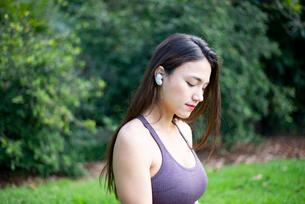 ワイヤレスイヤホンで音楽を聴いている女性の写真素材 [FYI03133378]