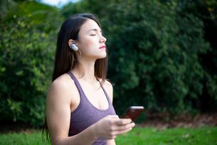 ワイヤレスイヤホンで音楽を聴いている女性の写真素材 [FYI03133384]