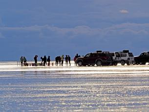 世界の絶景雨季の南米ボリビアウユニ塩湖で夕暮れを待つ観光客たちと移動用の四輪駆動車の写真素材 [FYI03134244]