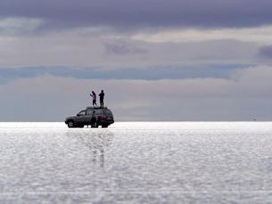 世界の絶景として知られる南米ボリビアウユニ塩湖の雨季に湖面に広がる水に小波が立ち光溢れる中、四輪駆動車の屋根に乗って景色を楽しむ観光客の写真素材 [FYI03134246]