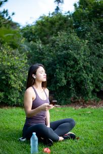 芝生に座ってワイヤレスイヤホンで音楽を聴いている女性の写真素材 [FYI03134721]