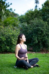 芝生に座ってワイヤレスイヤホンで音楽を聴いている女性の写真素材 [FYI03134848]