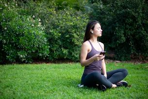 芝生に座ってワイヤレスイヤホンで音楽を聴いている女性の写真素材 [FYI03134849]