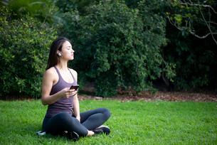 芝生に座ってワイヤレスイヤホンで音楽を聴いている女性の写真素材 [FYI03134850]