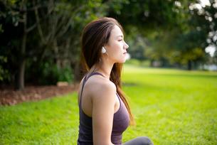 芝生に座ってワイヤレスイヤホンで音楽を聴いている女性の写真素材 [FYI03134884]