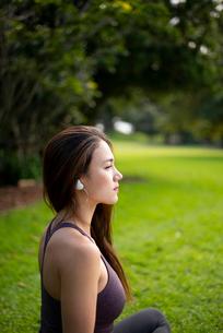 芝生に座ってワイヤレスイヤホンで音楽を聴いている女性の写真素材 [FYI03134886]