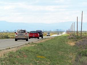 米コロラド州南部、ロッキー山脈が見える景色のローカル舗装道路を走る車の写真素材 [FYI03135317]