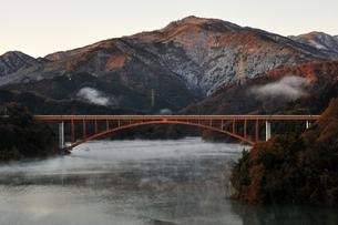 宮ヶ瀬湖から朝焼けの丹沢の山並みの写真素材 [FYI03135864]