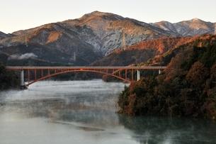 宮ヶ瀬湖から朝焼けの丹沢の山並みの写真素材 [FYI03135867]