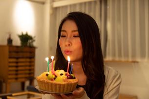 部屋の中でロウソクに火のついたケーキを持つ若い女性の写真素材 [FYI03136881]