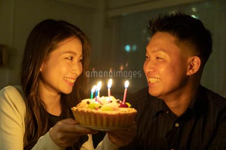 フルーツケーキで誕生日を祝う若いカップルの写真素材 [FYI03136926]