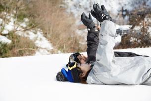 雪の上に寝そべって空に手をかざす二人の女性の写真素材 [FYI03137477]