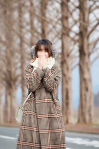 田舎道で寒そうにする女性の写真素材 [FYI03137500]