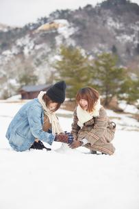雪の積もった広場で遊ぶ二人の女性の写真素材 [FYI03137511]