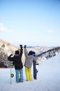 スノーボードを抱えてゲレンデで拳をあげる女性達の写真素材 [FYI03137522]