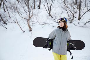 スノーボードを抱えて歩く女性の写真素材 [FYI03137524]