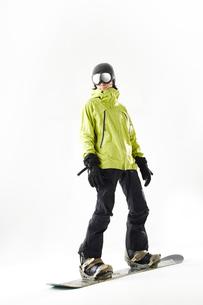 白バックでスノーボードをする男性の写真素材 [FYI03137537]