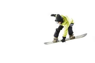白バックでスノーボードをする男性のジャンプ姿の写真素材 [FYI03137545]