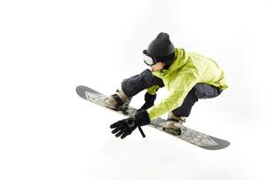 白バックでスノーボードをする男性のジャンプ姿の写真素材 [FYI03137546]