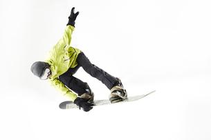 白バックでスノーボードをする男性のジャンプ姿の写真素材 [FYI03137547]