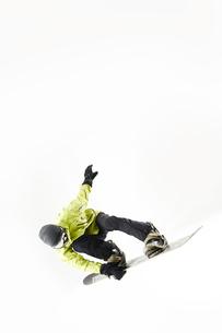 白バックでスノーボードをする男性のジャンプ姿の写真素材 [FYI03137548]