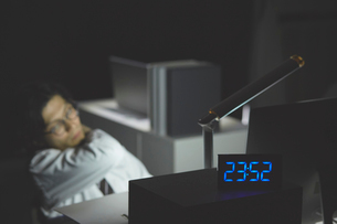 0時近くまで残業をして疲れている男性の写真素材 [FYI03137594]