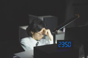 0時近くまで残業をして疲れている男性の写真素材 [FYI03137595]