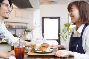 料理を運ぶ男女のカフェ店員の写真素材 [FYI03137614]