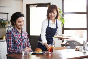 料理を提供するカフェ店員の写真素材 [FYI03137619]
