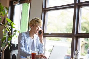 カフェで電話をしながらパソコンを操作する男性の写真素材 [FYI03137624]