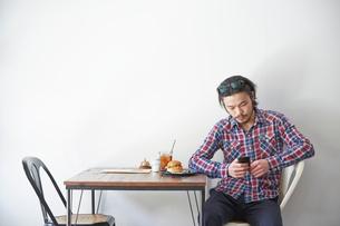 カフェでスマートフォンを操作する男性の写真素材 [FYI03137626]