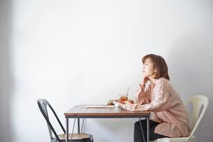 カフェでスマートフォンを操作する女性の写真素材 [FYI03137627]