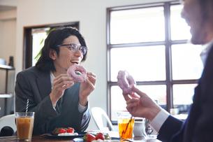 カフェドーナツに笑顔をこぼす2人のサラリーマンの写真素材 [FYI03137632]