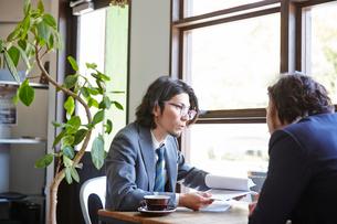 カフェで仕事の打ち合わせをする2人のサラリーマンの写真素材 [FYI03137635]